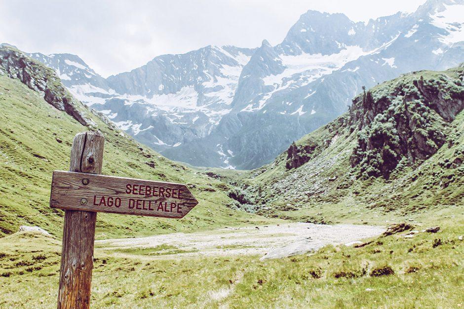 Ein Holzschild mit der Aufschrift Seebersee vor einer Bergkulisse