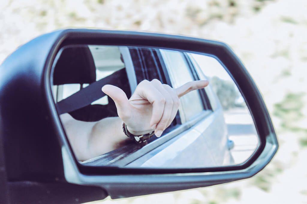 Hang Loose Zeichen in Seitenspiegel von Auto