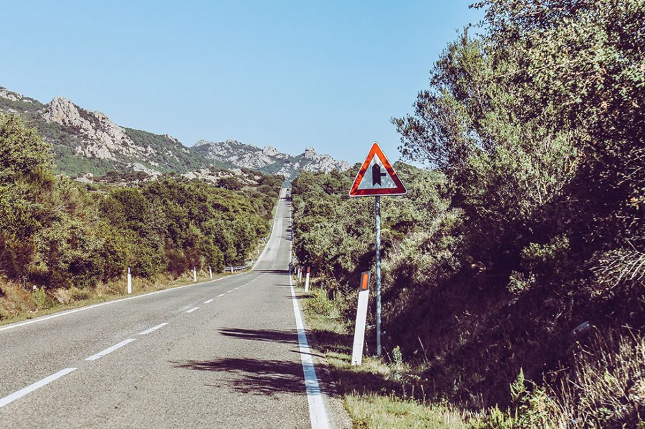 gerade Strasse mit Schild im Hinterland von Sardinien