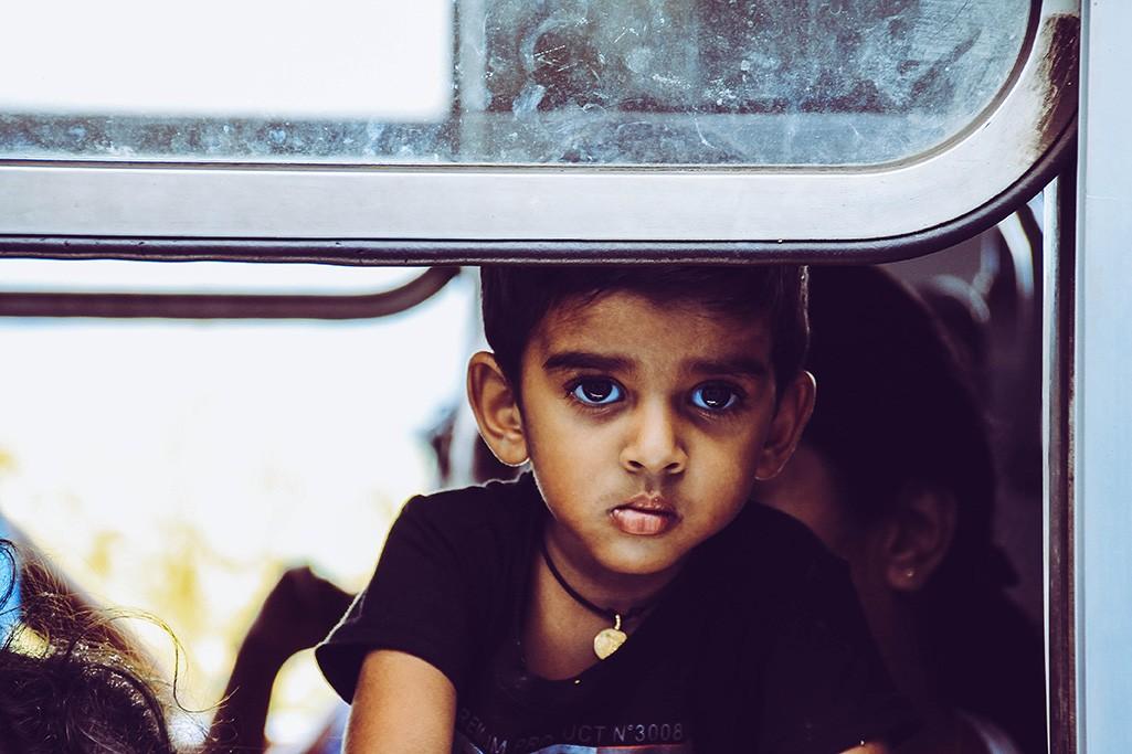 Kind blickt aus Zug in Sri Lanka