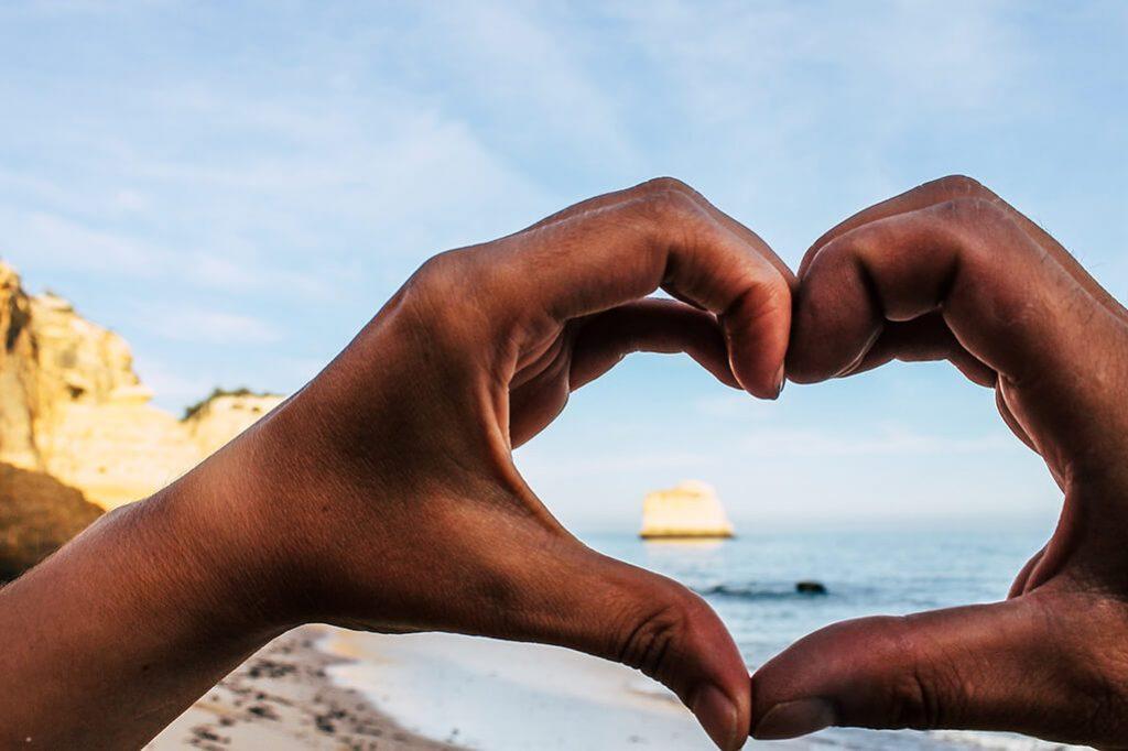 Personen formen mit Haenden ein Herz am Strand