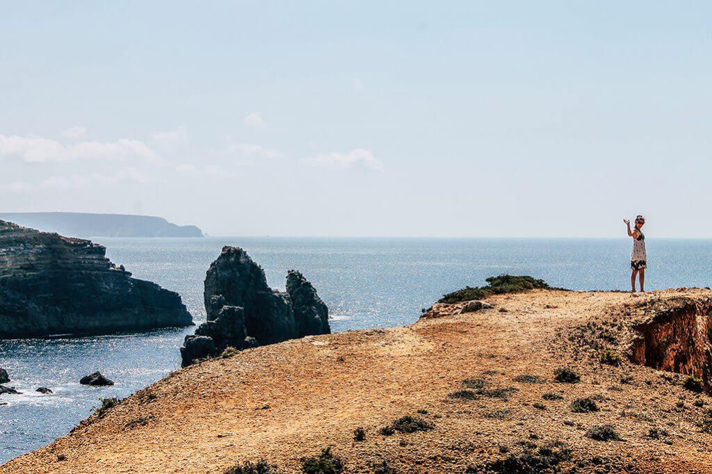 Person steht an Klippe an der Algarve und winkt