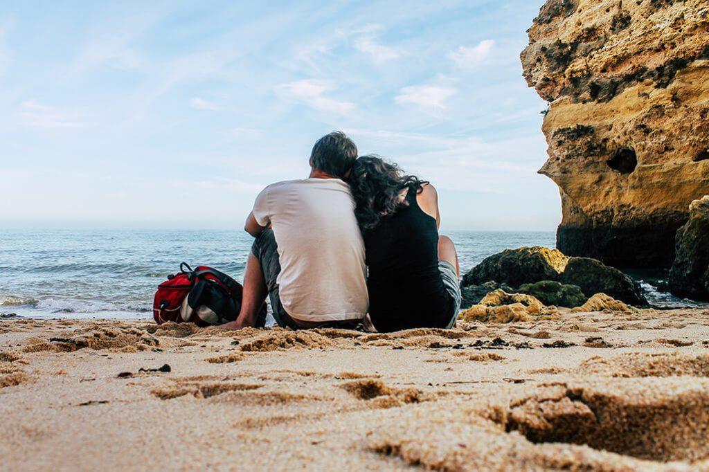 Liebespaar sitzt an Kueste an der Algarve nebeneinander
