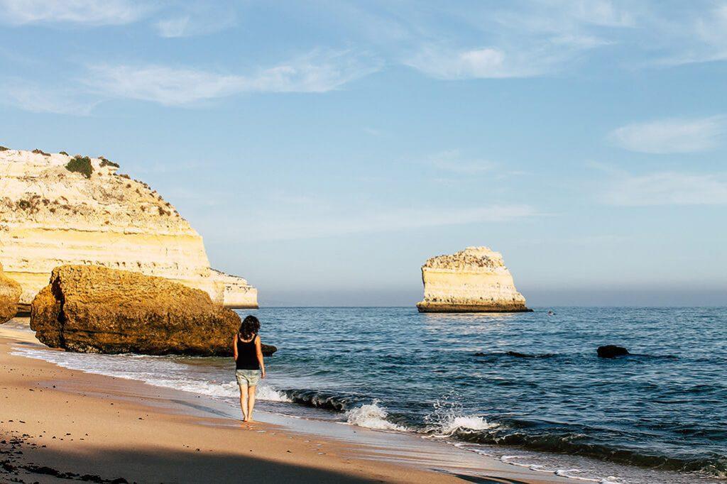 Person geht an Strand mit Felsen im Hintergrund spazieren