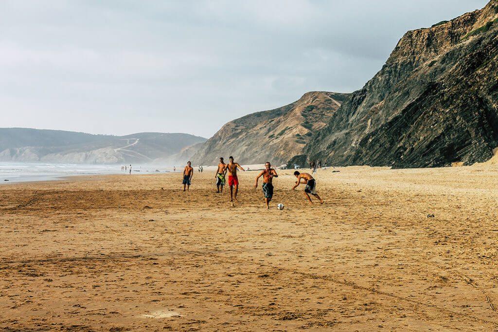 Maenner spielen am Praia de Vale Figueiras Fussball