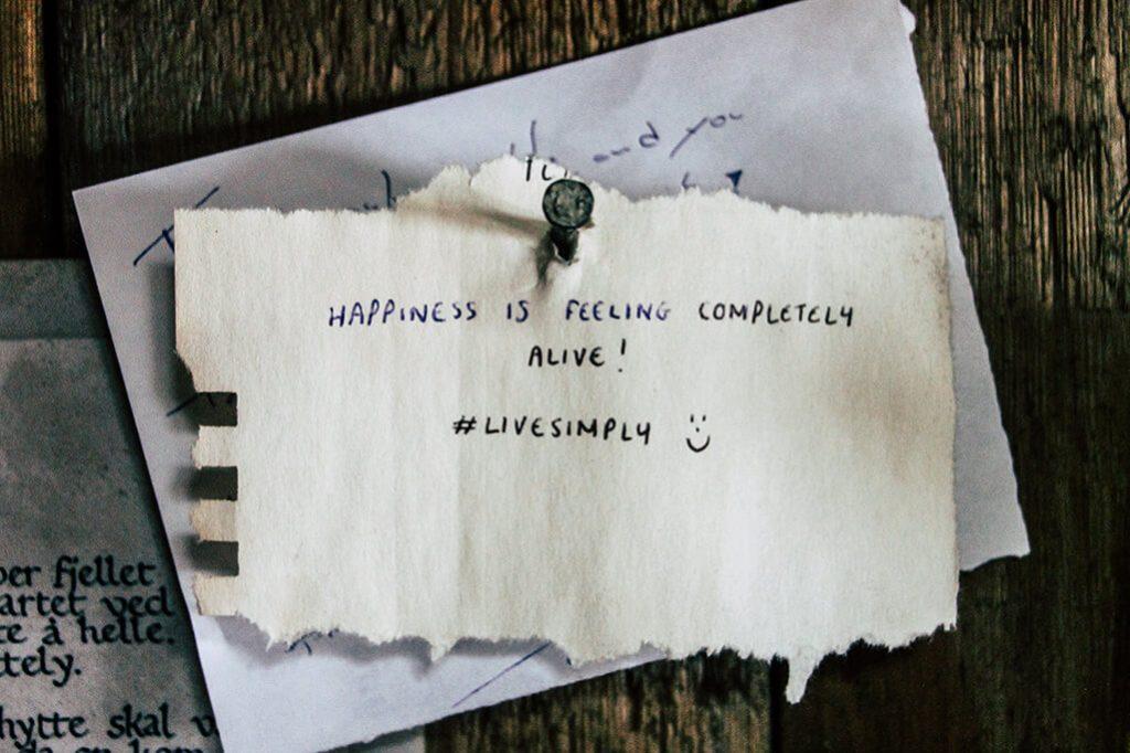 Ein Zettel mit der Aufschrift Happiness is feeling completely alive.