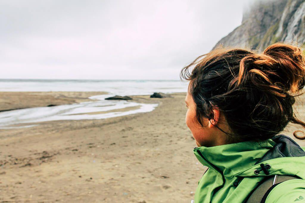 Person geniesst Aussicht am Kvalvika Strand auf den Lofoten