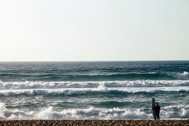 Surfer am Strand vor dem Meer