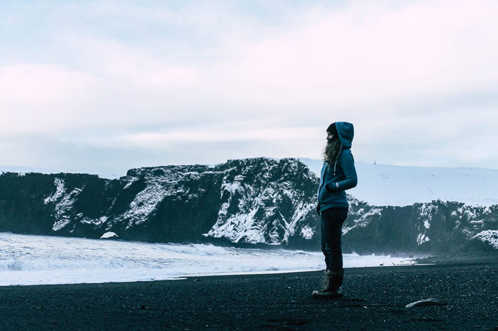 Person am schwarzen Strand auf Island