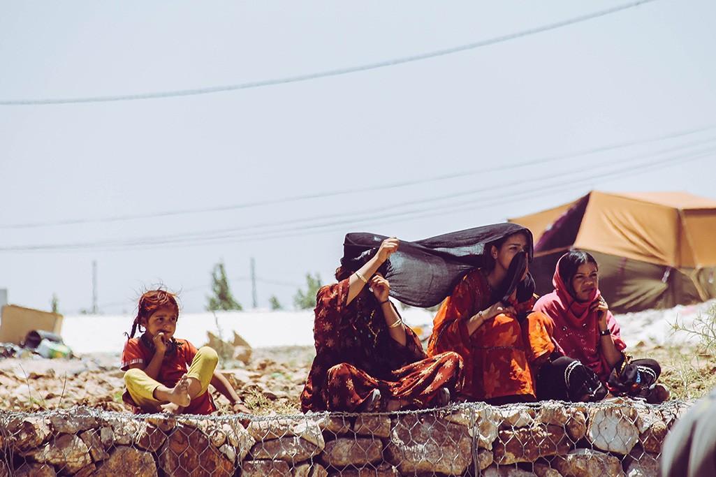 Kinder sitzen auf Mauer in Amman
