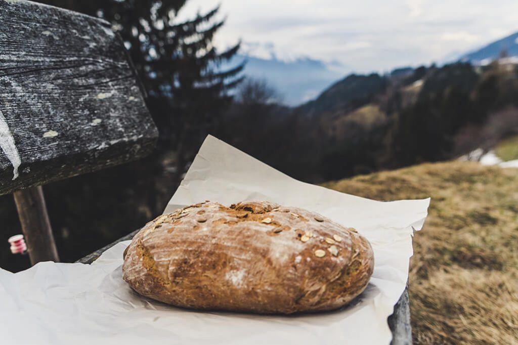 frisches Brot auf Holzbank mit Bergen im Hintergrund