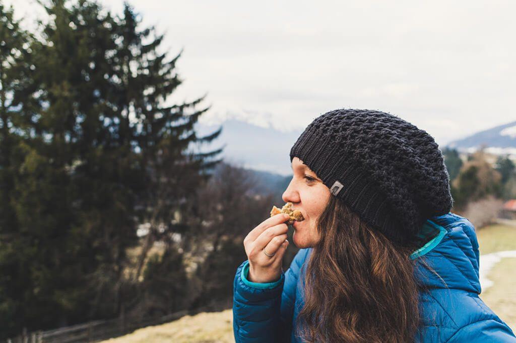 Person ist Brot mit Bergen im Hintergrund