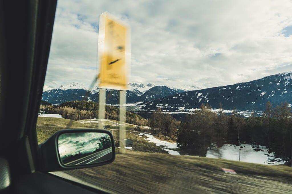 Blick aus dem Seitenfenster eines Autos auf die Berge