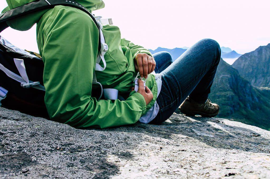 Person sitzt auf Felsblock und geniesst Aussicht