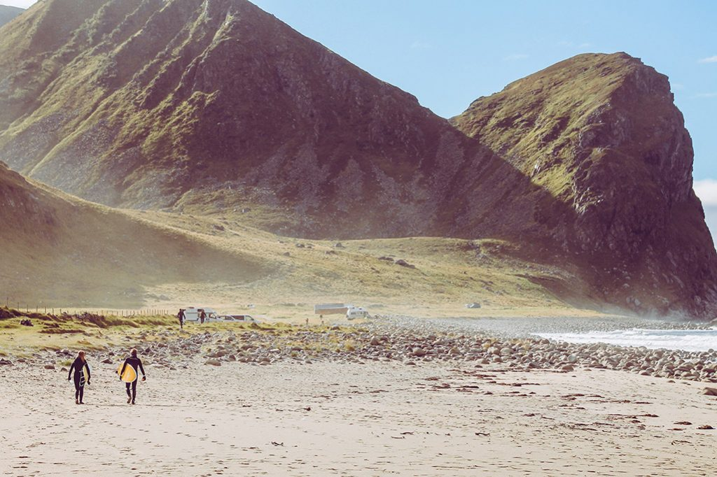 Surfer laufen am Strand bei Unstad entlang