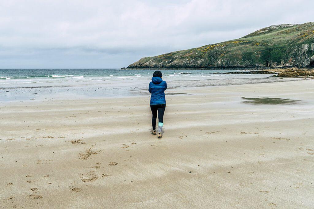Person am Strand der Church Bay auf der Insel Anglesey