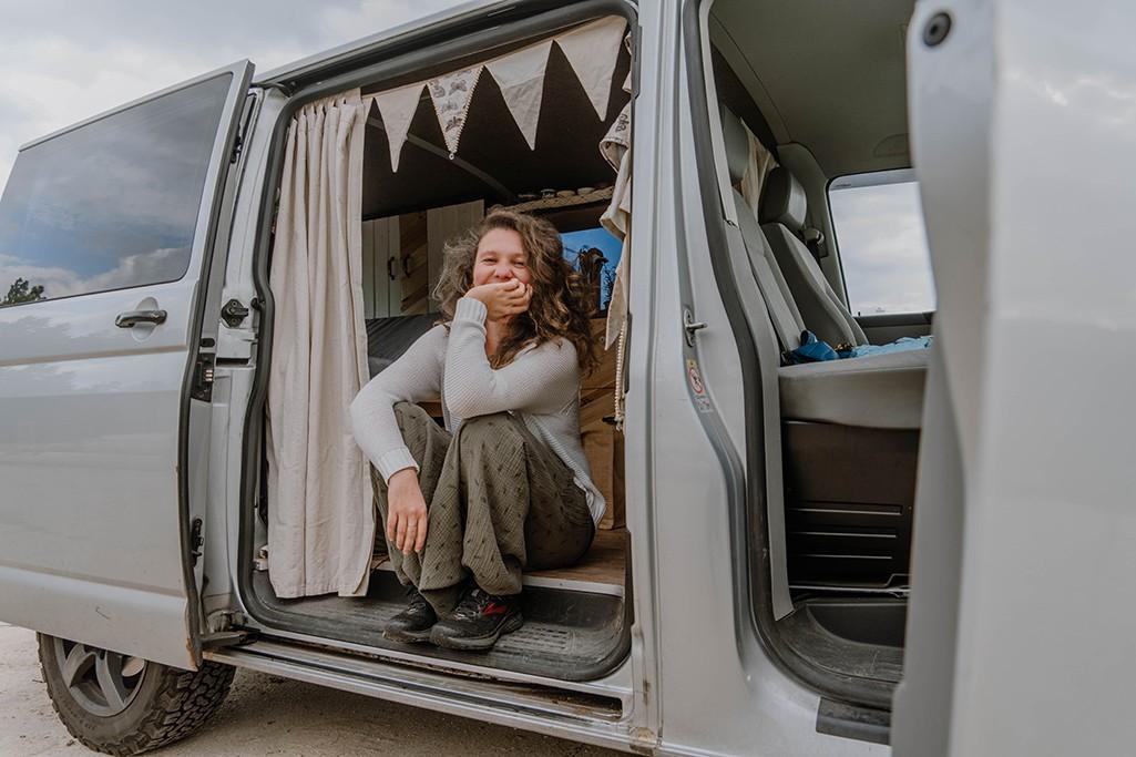 Frau sitzt in VW T5 Camper