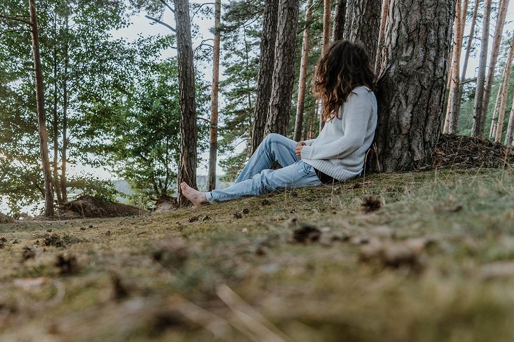 Person sitzt barfuß an Baum