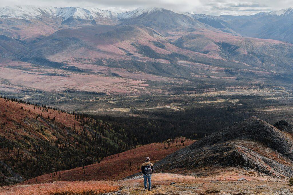 Person geniesst aussicht ueber den Tombstone Territorial Park