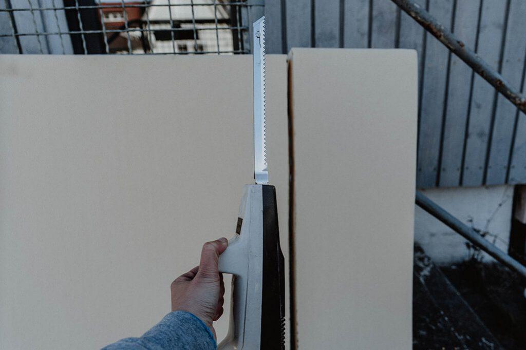Schaummatratze mit elektrischem Kuechenmesser schneiden