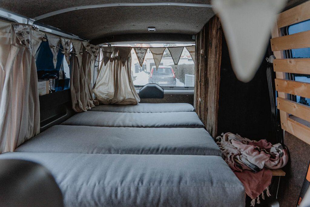 Blick in VW Bus mit ausgeklapptem Bett