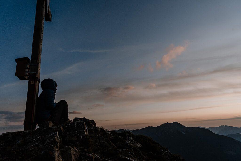 Person sitzt an Grubigstein Gipfelkreuz