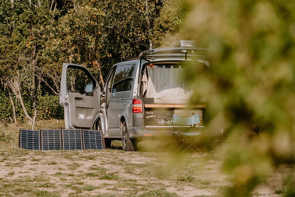 silberner VW T5 Camper von hinten, mit faltbarer Solartasche von Wattstunde seitlich daneben