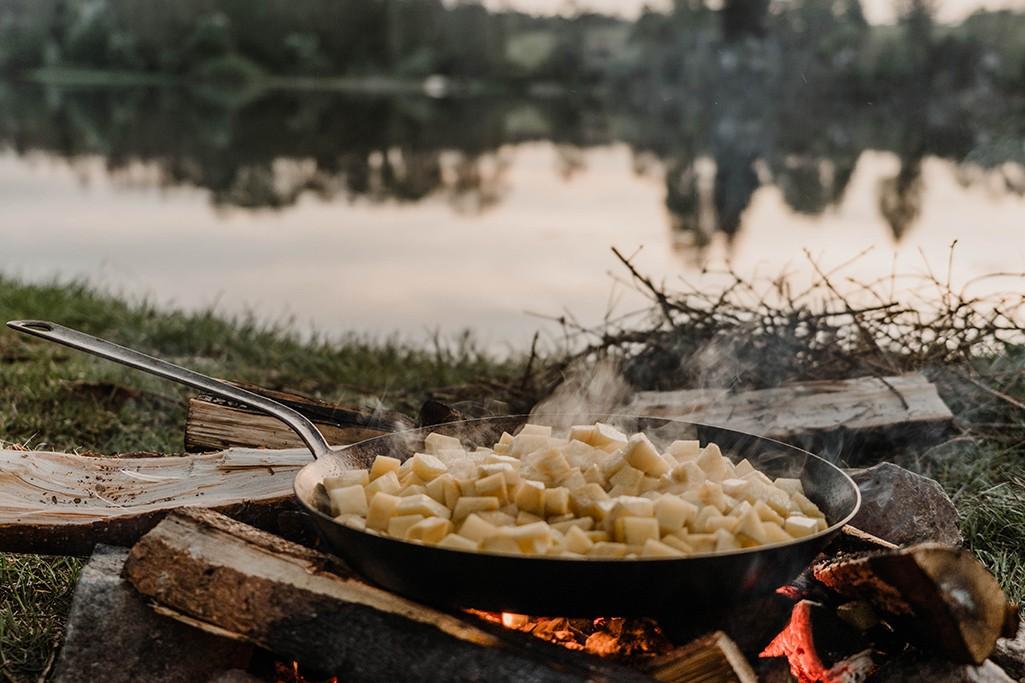Pfanne mit Bratkartoffeln auf Lagerfeuer