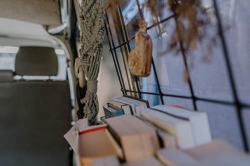 Detailaufnahme Bücherregal in Camper mit Gitter vor Fenster